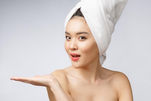 Retrato hermosa mujer asiática wow sorprendida y señalando la mano hacia el lado derecho