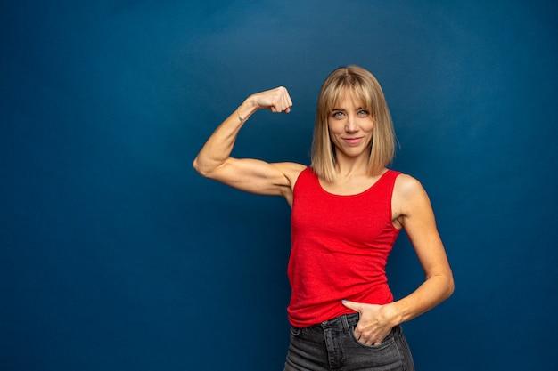 Retrato de hermosa mujer atlética caucásica en camiseta roja mostrando bíceps de su mano.