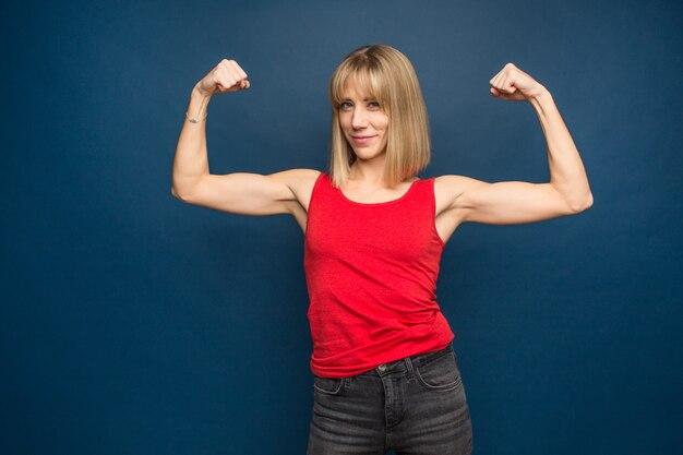 Retrato de hermosa mujer atlética caucásica en camiseta roja mostrando bíceps de sus manos.