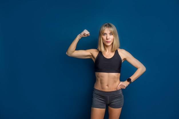 Retrato de hermosa mujer atlética caucásica en sujetador deportivo y pantalones cortos mostrando bíceps de su mano.