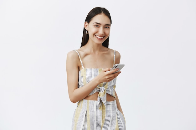 Retrato de hermosa mujer bronceada amable y encantadora en top a juego con pantalones cortos, sosteniendo un teléfono inteligente y mirando con alegría, amoroso nuevo teléfono sobre pared gris