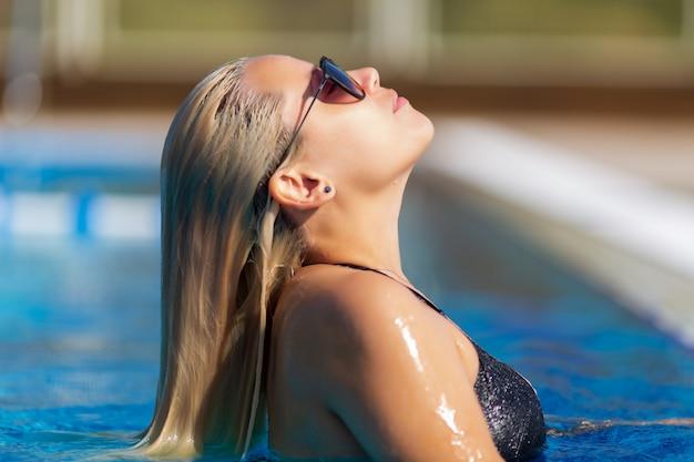 Retrato de hermosa mujer bronceada en traje de baño negro y gafas de sol relajantes en el spa de la piscina
