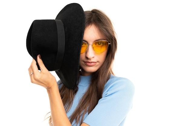 Retrato de hermosa mujer caucásica con cabello largo oscuro en camiseta azul con sombrero negro