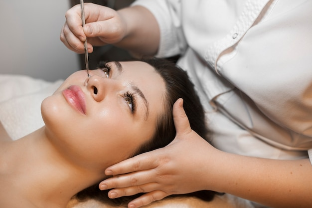 Retrato de hermosa mujer caucásica con cabello oscuro apoyado en una cama de spa con limpieza facial por una cosmetóloga en el salón de spa de bienestar.