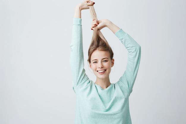Retrato de hermosa mujer caucásica en camisa azul claro, jugando con el pelo largo y rubio.