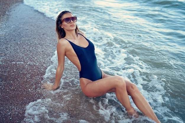 Retrato de hermosa mujer caucásica sexy bronceada en gafas de sol con estampado de leopardo con el pelo largo en traje de baño tumbado en la playa de verano