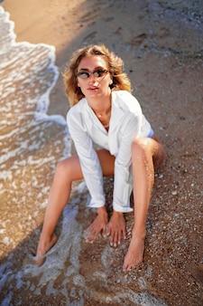 Retrato de hermosa mujer caucásica sexy bronceada en gafas de sol con el pelo largo en traje de baño y camiseta blanca tumbado en la playa de verano