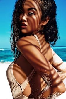 Retrato de hermosa mujer caucásica tomar el sol modelo con cabello largo y oscuro en traje de baño beige posando en la playa de verano con arena blanca en el cielo azul y el océano