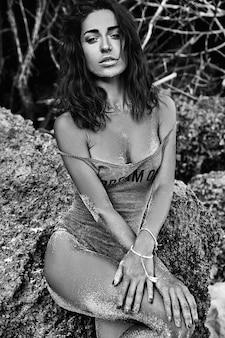 Retrato de hermosa mujer caucásica tomar el sol modelo con cabello largo y oscuro en traje de baño posando cerca de rocas en la playa