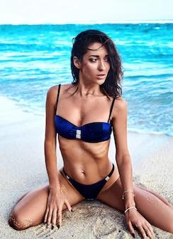 Retrato de hermosa mujer caucásica tomar el sol modelo con cabello largo y oscuro en traje de baño posando en la playa de verano con arena blanca sobre fondo azul del cielo y el océano