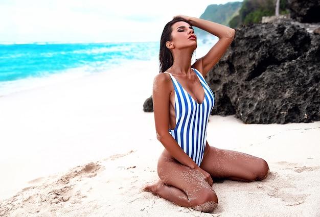 Retrato de hermosa mujer caucásica tomar el sol modelo con cabello largo y oscuro en traje de baño a rayas posando en la playa de verano con arena blanca