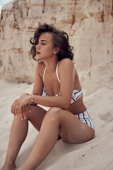 Retrato de hermosa mujer caucásica tomar el sol modelo con cabello largo oscuro en traje de baño a rayas tumbado en la playa de verano con arena blanca. vista superior