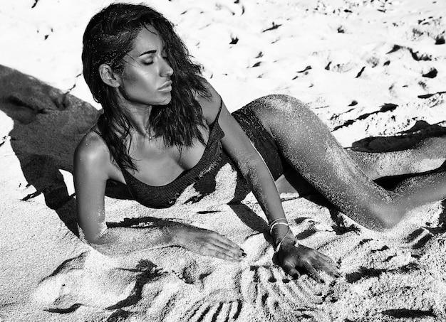 Retrato de hermosa mujer caucásica tomar el sol modelo con cabello largo y oscuro en traje de baño tumbado en la playa de verano con arena blanca
