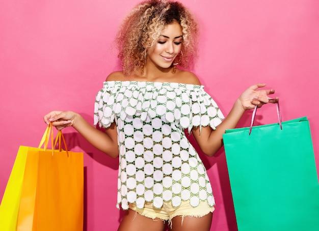 Retrato de hermosa mujer compradora compulsiva sonriente sosteniendo coloridas bolsas de papel