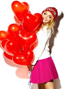 Retrato de hermosa mujer dulce feliz linda mujer rubia sonriente en ropa casual hipster, en falda rosa y gorro cálido de invierno con globos de corazón rojo en las manos