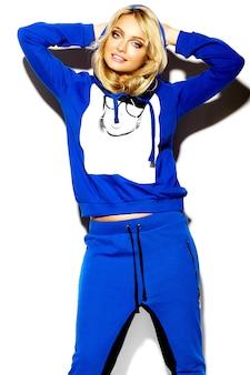 Retrato de hermosa mujer dulce feliz sonriente mujer rubia en ropa deportiva casual hipster azul