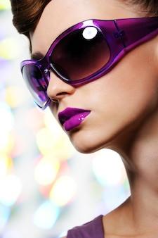 Retrato de hermosa mujer elegante en gafas de sol violetas de moda