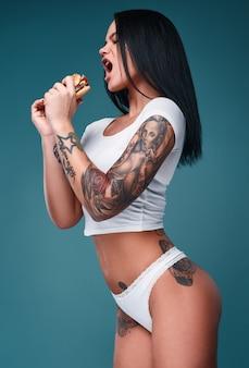 Retrato de hermosa mujer encantadora con tatuajes sosteniendo una hamburguesa