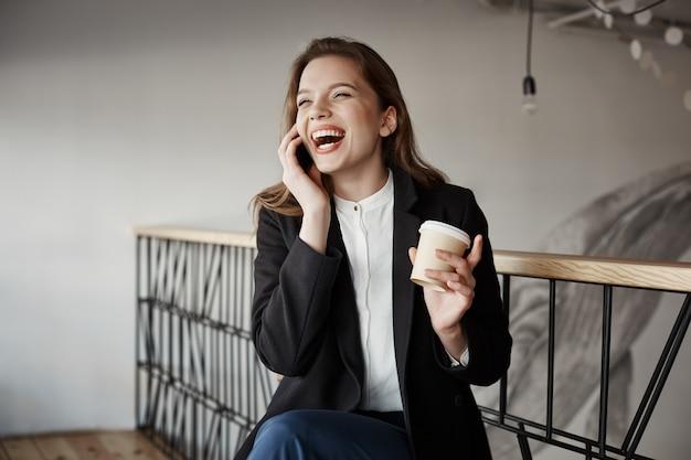 Retrato de hermosa mujer europea inteligente sentado en la cafetería, tomando café y gesticulando mientras habla por teléfono inteligente