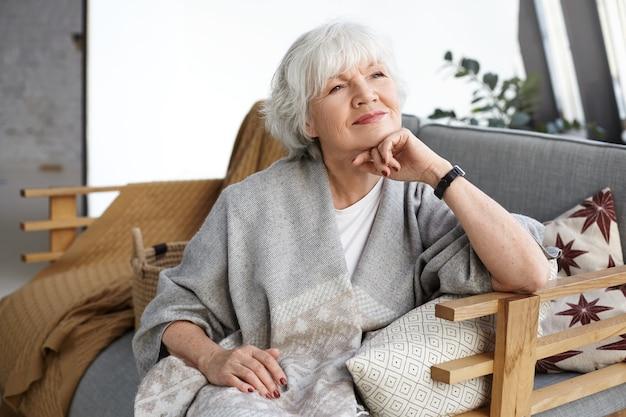 Retrato de hermosa mujer europea de pelo gris de mediana edad con sonrisa de ensueño y ojos llenos de sabiduría relajándose solo en casa, sentada en un cómodo sofá, recordando los días de su juventud
