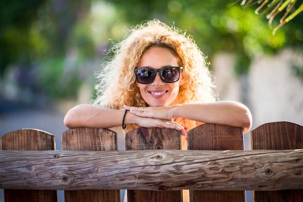 Retrato de hermosa mujer feliz alegre con sol a contraluz y bonita sonrisa mirando a la cámara