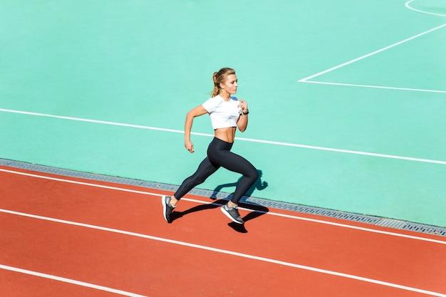 Retrato de una hermosa mujer fitness corriendo en el estadio