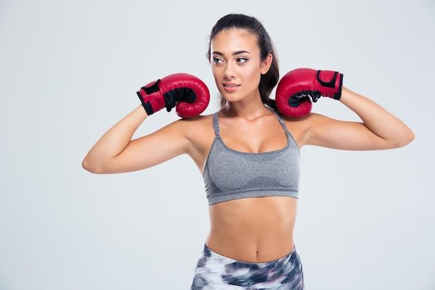 Retrato de una hermosa mujer fitness de pie en guantes de boxeo aislado en una pared blanca