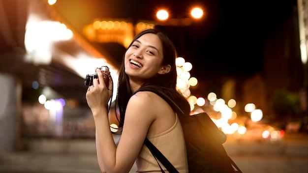Retrato de hermosa mujer fotógrafa en la ciudad por la noche