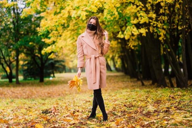 Retrato de una hermosa mujer joven adulta en el fondo del otoño en el parque en mascarilla médica