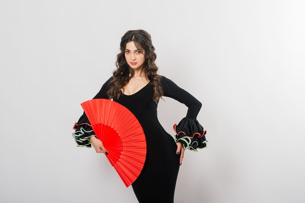 Retrato de hermosa mujer joven bailando flamenco con ventilador en estudio