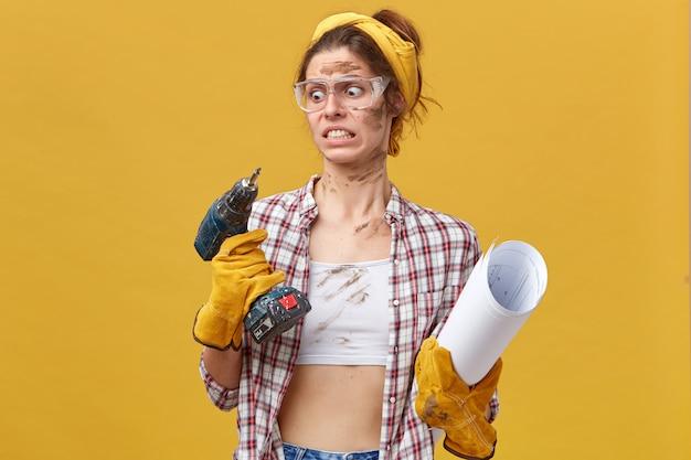 Retrato de hermosa mujer joven con camisa, top blanco y gafas protectoras con taladro y papel enrollado mirando con mirada repugnante a la máquina perforadora aislada sobre pared amarilla