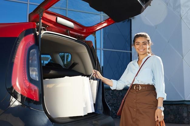 Retrato de hermosa mujer joven cargando bolsas de compras en el coche y sonriendo a la cámara mientras está de pie en el estacionamiento del centro comercial