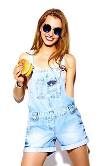 Retrato de hermosa mujer joven elegante comiendo hamburguesas