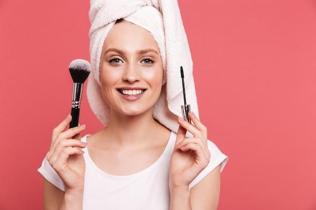 Retrato de hermosa mujer joven envuelta en una toalla blanca después de la ducha aplicando cosméticos con pincel de maquillaje aislado sobre pared rosa