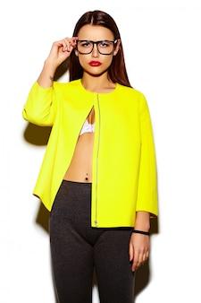 Retrato de hermosa mujer joven con estilo en abrigo amarillo y con gafas
