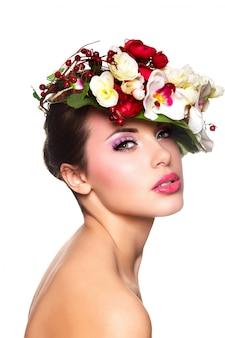 Retrato de hermosa mujer joven con estilo con coloridas flores en la cabeza.