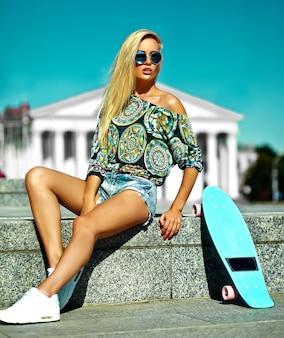 Retrato de hermosa mujer joven con estilo con patineta