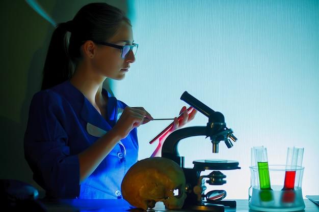 Retrato de hermosa mujer joven en un laboratorio sentado en su lugar de trabajo.
