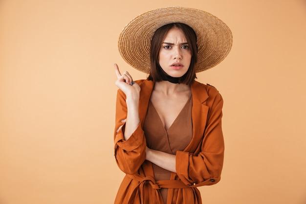 Retrato de una hermosa mujer joven molesta con sombrero de paja que se encuentran aisladas sobre la pared beige, con los brazos cruzados