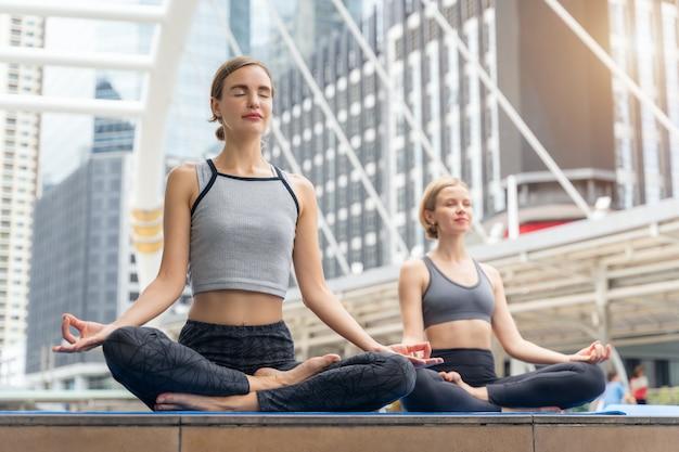 Retrato de hermosa mujer joven practicando yoga al aire libre en la ciudad.