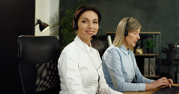 Retrato de hermosa mujer joven de raza blanca en auriculares trabajando en equipo en call center.