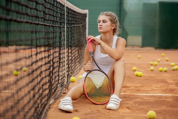 Retrato de hermosa mujer joven sentada cerca de la red en la cancha de tenis con pelota al aire libre.