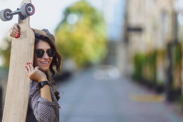 Retrato de hermosa mujer joven sentada en el suelo y sosteniendo un longboard en el clima soleado de la calle de la ciudad.