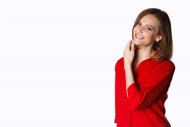 Retrato de hermosa mujer joven sonriente de pie en una camisa roja aislada