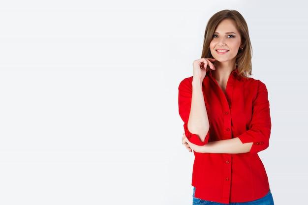 Retrato de hermosa mujer joven sonriente de pie en una camisa roja y jeans azul aislado