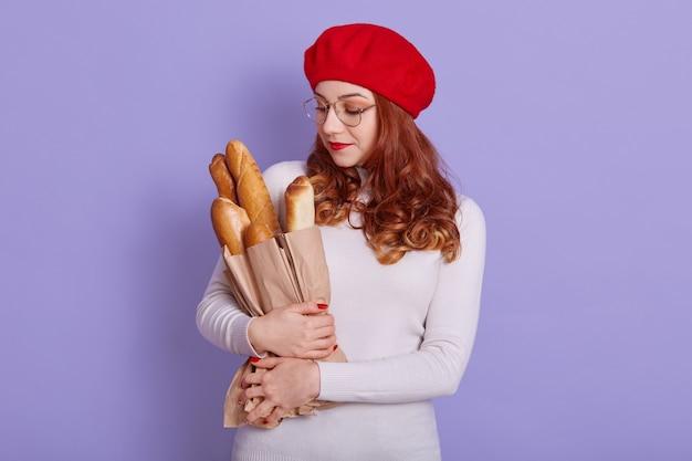 Retrato de hermosa mujer joven sosteniendo una bolsa de papel con pan en el espacio lila