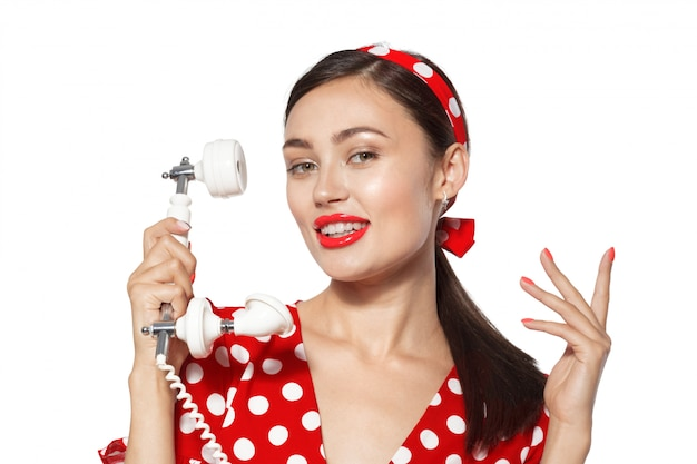 Retrato de hermosa mujer joven con teléfono, vestida en estilo pin-up.