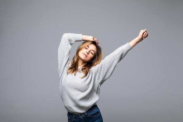 Retrato de una hermosa mujer joven usar suéter manteniendo los brazos levantados de pie contra la pared gris