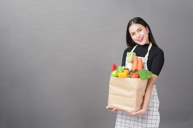 Retrato de hermosa mujer joven con verduras en la bolsa de la compra en el estudio de fondo gris