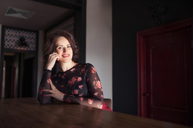 Retrato de hermosa mujer madura sentada en la cafetería mirando a otro lado. mujer madura feliz alegre relajante en el café y sonriendo. copia espacio